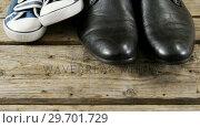 Купить «Pairs of new shoes on wooden plank», видеоролик № 29701729, снято 13 января 2017 г. (c) Wavebreak Media / Фотобанк Лори