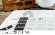 Купить «Coffee cup with date block arranged on wooden plank», видеоролик № 29701745, снято 13 января 2017 г. (c) Wavebreak Media / Фотобанк Лори