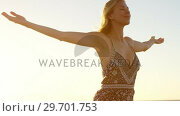 Купить «Woman with arms outstretched standing on the beach», видеоролик № 29701753, снято 1 марта 2017 г. (c) Wavebreak Media / Фотобанк Лори