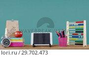 Купить «School accessories with digital tablet, lunch and alarm clock on table», видеоролик № 29702473, снято 5 апреля 2017 г. (c) Wavebreak Media / Фотобанк Лори