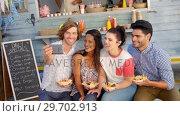 Купить «Friends taking selfie from mobile phone in food truck van», видеоролик № 29702913, снято 26 марта 2017 г. (c) Wavebreak Media / Фотобанк Лори