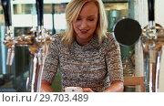 Купить «Beautiful woman using mobile phone at bar counter 4k», видеоролик № 29703489, снято 28 марта 2017 г. (c) Wavebreak Media / Фотобанк Лори