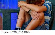 Купить «Sad schoolboy sitting in locker room on bench 4k», видеоролик № 29704005, снято 11 марта 2017 г. (c) Wavebreak Media / Фотобанк Лори