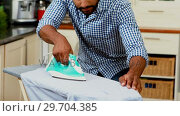 Купить «Mid section of man ironing clothes in kitchen 4k», видеоролик № 29704385, снято 20 марта 2017 г. (c) Wavebreak Media / Фотобанк Лори