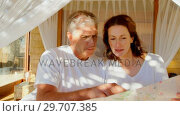Couple looking at map while relaxing on canopy bed 4k. Стоковое видео, агентство Wavebreak Media / Фотобанк Лори