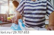 Купить «Senior woman ironing clothes in the kitchen 4K 4k», видеоролик № 29707653, снято 20 марта 2017 г. (c) Wavebreak Media / Фотобанк Лори