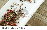 Купить «Black pepper in tray on wooden plank 4k», видеоролик № 29707689, снято 5 июня 2017 г. (c) Wavebreak Media / Фотобанк Лори