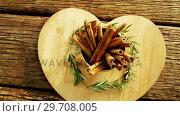 Купить «Cinnamon sticks and rosemary arranged on wooden board 4k», видеоролик № 29708005, снято 5 июня 2017 г. (c) Wavebreak Media / Фотобанк Лори
