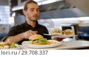 Купить «Chef keeping plates of burger on the order station 4k», видеоролик № 29708337, снято 21 мая 2017 г. (c) Wavebreak Media / Фотобанк Лори