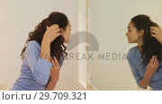 Купить «Young woman standing in front of mirror getting her hair done 4K 4k», видеоролик № 29709321, снято 31 мая 2017 г. (c) Wavebreak Media / Фотобанк Лори