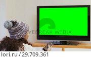 Купить «Smiling woman in warm clothing watching television 4K 4k», видеоролик № 29709361, снято 31 мая 2017 г. (c) Wavebreak Media / Фотобанк Лори