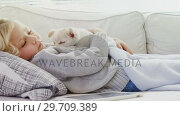 Купить «Little girl sleeping on sofa holding her pet in her arms 4K 4k», видеоролик № 29709389, снято 31 мая 2017 г. (c) Wavebreak Media / Фотобанк Лори