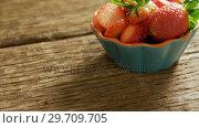 Купить «Bowl full of slice strawberries on wooden floor 4K 4k», видеоролик № 29709705, снято 12 июня 2017 г. (c) Wavebreak Media / Фотобанк Лори