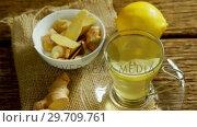 Купить «Lemon tea with ginger and lemon on wooden table 4k», видеоролик № 29709761, снято 12 июня 2017 г. (c) Wavebreak Media / Фотобанк Лори
