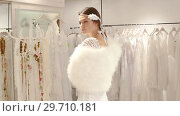 Купить «Сheerful young woman dressed in luxury white gown standing in wedding shop», видеоролик № 29710181, снято 16 октября 2018 г. (c) Яков Филимонов / Фотобанк Лори