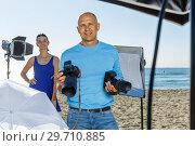 Купить «Portrait of smiling photographer with his camera during photo shooting on sea coast», фото № 29710885, снято 5 октября 2018 г. (c) Яков Филимонов / Фотобанк Лори