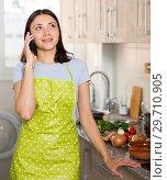 Купить «Young girl housewife in apron talking by phone at home kitchen», фото № 29710905, снято 18 апреля 2018 г. (c) Яков Филимонов / Фотобанк Лори