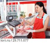 Купить «Female seller weighing sausages in shop», фото № 29711077, снято 22 июня 2018 г. (c) Яков Филимонов / Фотобанк Лори