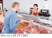 Купить «seller helping attentive customer choosing different sausages», фото № 29711081, снято 22 июня 2018 г. (c) Яков Филимонов / Фотобанк Лори