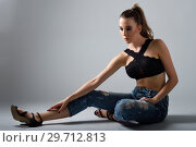 Купить «Young woman wearing black bra and blue jeans sitting on floor. Studio shot.», фото № 29712813, снято 25 июля 2017 г. (c) Ingram Publishing / Фотобанк Лори