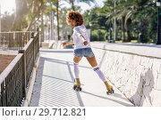 Купить «Black woman, afro hairstyle, on roller skates riding near the beach.», фото № 29712821, снято 20 декабря 2017 г. (c) Ingram Publishing / Фотобанк Лори