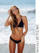 Купить «Young blonde woman with beautiful body in swimwear smiling on a tropical beach. », фото № 29712961, снято 24 сентября 2017 г. (c) Ingram Publishing / Фотобанк Лори
