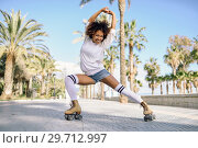 Купить «Black woman on roller skates rollerblading in beach promenade with palm trees», фото № 29712997, снято 20 декабря 2017 г. (c) Ingram Publishing / Фотобанк Лори