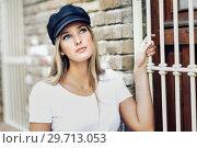 Купить «Young blonde woman wearing cap standing near a brick wall.», фото № 29713053, снято 20 сентября 2017 г. (c) Ingram Publishing / Фотобанк Лори