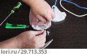 Купить «Мастер ремонтирует утюг. Руки мужчины крупным планом», видеоролик № 29713353, снято 8 ноября 2017 г. (c) Олег Хархан / Фотобанк Лори