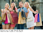 Купить «Portrait of three girls and one man standing with shopping bags», фото № 29713521, снято 23 января 2019 г. (c) Яков Филимонов / Фотобанк Лори