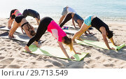 Купить «Sporty people practicing yoga on beach», фото № 29713549, снято 14 июня 2017 г. (c) Яков Филимонов / Фотобанк Лори