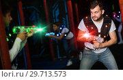 Купить «Emotional guy playing laser tag in colorful beams», фото № 29713573, снято 25 апреля 2018 г. (c) Яков Филимонов / Фотобанк Лори