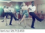 Купить «Young positive people practicing vigorous jive movements in dance class», фото № 29713653, снято 4 октября 2018 г. (c) Яков Филимонов / Фотобанк Лори
