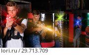 Купить «Young guy holding colored laser guns and took aim during laser t», фото № 29713709, снято 23 августа 2018 г. (c) Яков Филимонов / Фотобанк Лори