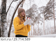 Купить «Girl in a sweater holding a paper cup with a hot drink in a winter park», фото № 29714589, снято 13 января 2019 г. (c) Евгений Харитонов / Фотобанк Лори
