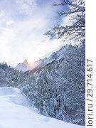 Купить «Солнечный луч освещает заснеженную горную вершину Чёрный Зуб Софруджу Главного Кавказского хребта около курортного поселка Домбай», фото № 29714617, снято 15 декабря 2018 г. (c) Наталья Гармашева / Фотобанк Лори