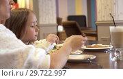 Купить «Side View - A Cute Young Mother And A Cute Little Daughter Eat Together», видеоролик № 29722997, снято 20 мая 2019 г. (c) Pavel Biryukov / Фотобанк Лори