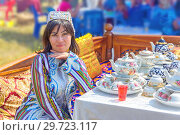 Купить «Russia, Samara, July, 2018: A young beautiful brunette girl in Uzbek national attire sells tea sets at the fair.», фото № 29723117, снято 29 июля 2018 г. (c) Акиньшин Владимир / Фотобанк Лори