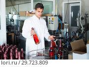 Купить «Glad man holding newly produced bottle of wine», фото № 29723809, снято 21 сентября 2016 г. (c) Яков Филимонов / Фотобанк Лори
