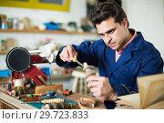 Купить «Craftsman in uniform working in carpentry», фото № 29723833, снято 8 апреля 2017 г. (c) Яков Филимонов / Фотобанк Лори