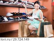 Купить «Charming woman is choosing sport shoes for jogging», фото № 29724149, снято 10 мая 2017 г. (c) Яков Филимонов / Фотобанк Лори