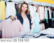 Купить «Young female customer selecting new garments», фото № 29724161, снято 19 июня 2017 г. (c) Яков Филимонов / Фотобанк Лори