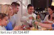 Купить «happy family having dinner party at home», видеоролик № 29724497, снято 8 января 2019 г. (c) Syda Productions / Фотобанк Лори