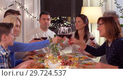 Купить «happy family having dinner party at home», видеоролик № 29724537, снято 8 января 2019 г. (c) Syda Productions / Фотобанк Лори