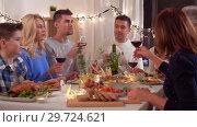 Купить «happy family having dinner party at home», видеоролик № 29724621, снято 7 января 2019 г. (c) Syda Productions / Фотобанк Лори