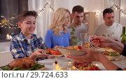 Купить «happy family having dinner party at home», видеоролик № 29724633, снято 7 января 2019 г. (c) Syda Productions / Фотобанк Лори