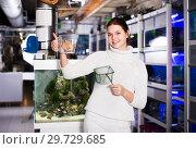 Купить «Girl holding net for aquarian fishes and water container with big colorful fish inside», фото № 29729685, снято 17 февраля 2017 г. (c) Яков Филимонов / Фотобанк Лори