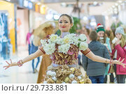 Купить «Russia, Samara, February 2018: the festival of plasticine rain. A girl in a beautiful dress decorated with flowers and Christmas balls.», фото № 29733881, снято 23 февраля 2018 г. (c) Акиньшин Владимир / Фотобанк Лори