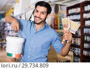 Купить «Man standing amongst racks in paint store with brushes and paint», фото № 29734809, снято 13 сентября 2017 г. (c) Яков Филимонов / Фотобанк Лори