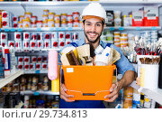 Купить «Workman holding basket with picked tools in paint store», фото № 29734813, снято 13 сентября 2017 г. (c) Яков Филимонов / Фотобанк Лори
